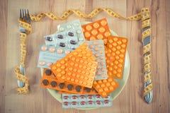 Blåsor av minnestavlor eller tillägg på plattan och gaffeln med kniven slogg in cm-, hälsovård- och bantningbegrepp Royaltyfri Bild