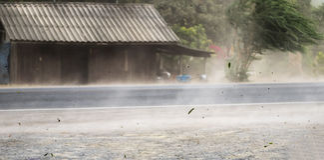 Blåste damm och sidor för vind storm på vägen arkivfoton