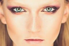 Blått öga av kvinnan med härliga guld- skuggor och svart eyelinermakeup Klassiskt smink Perfekta krön näsa och kanter royaltyfria bilder