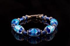 Blått armband på svart Royaltyfria Bilder