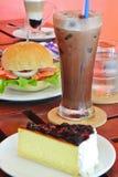 Blått bärostkaka och hamburgare och kaffe i frukost Royaltyfria Bilder