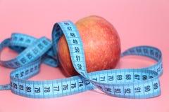 Blått band för att mäta kroppen runt om ett äpple royaltyfria bilder