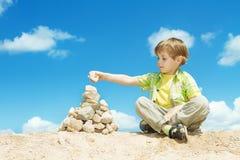 blått barn för ans över skystenar Arkivbild