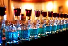 Blått bombarderar drinkskottexponeringsglas som står på falla för räknare Arkivbilder