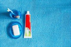 Blått exponeringsglas med tandborstar, röret av tandkräm och tvålmaträtt w Fotografering för Bildbyråer