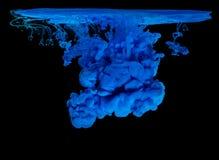 Blått färgpulver i vatten som skapar abstrakt form Arkivfoto