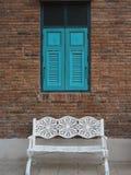 Blått fönster som göras av trä på den gamla tegelstenväggen med bänken för vit metall royaltyfria bilder
