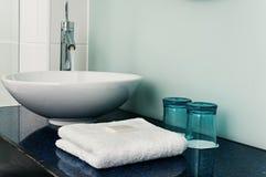 Blått för exponeringsglas för vatten för handdukar för badrumvaskräknare Royaltyfria Foton