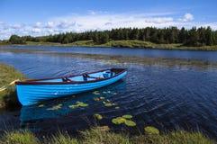 Blått fartyg i en sjö Arkivbild