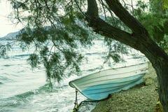 Blått fartyg och träd på stranden Begrepp - semester, turism G Arkivfoto