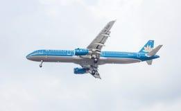 Blått flygplan i himlen Arkivbild