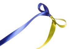 Blått-guling flerfärgat tygband och pilbåge som isoleras på en vit bakgrund Royaltyfri Fotografi