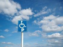 Blått handikapp som parkerar med vita moln och bakgrund för blå himmel arkivfoton