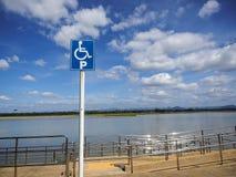 Blått handikapp som parkerar med vita moln och bakgrund för blå himmel royaltyfria foton