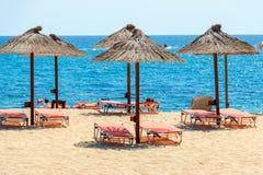 Blått hav, guld- sand och sunbeds på stranden Arkivfoto