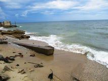 Blått hav på gryning, konstruktionsskräp, förorening av naturen, vågor med lamm och stranden med snäckskal arkivfoton