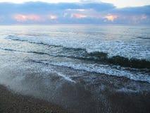 Blått hav, vågor med lamm och strand med snäckskal arkivfoto