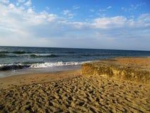 Blått hav, vågor med lamm och strand med snäckskal royaltyfria foton