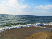 Blått hav, vågor med lamm och strand med snäckskal, spår på sanden arkivfoto