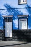 Blått hus med vita dörrar arkivfoto