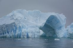 Blått isberg med passagen igenom royaltyfria foton