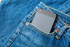 Blått jeanfack med mobilen Royaltyfri Foto