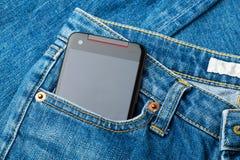 Blått jeanfack med mobilen Arkivbild