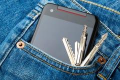 Blått jeanfack med mobilen och tangent Royaltyfri Bild