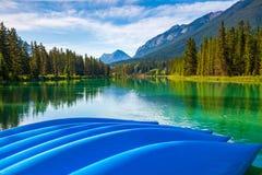 Blått kanotar på kusten av pilbågefloden i den Banff nationalparken royaltyfri bild