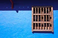 blått kolonialt fönster för detaljhusvägg Arkivfoto