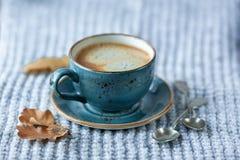 Blått koppwhithkaffe, stucken tröja, höstsidor på trä arkivfoton