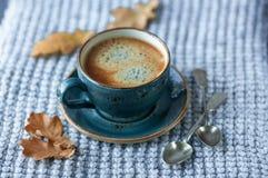 Blått koppwhithkaffe, stucken tröja, höstsidor på träbakgrund royaltyfri fotografi