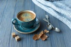 Blått koppwhithkaffe, stucken tröja, höstsidor på träbakgrund fotografering för bildbyråer