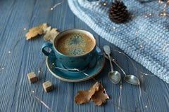 Blått koppwhithkaffe, stucken tröja, höstsidor på träbakgrund royaltyfri foto