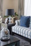 Blått kudde på soffan med den svarta lampan i vardagsrum royaltyfria bilder
