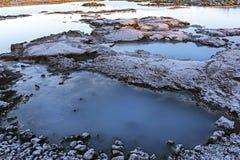 Blått lagunvatten i vulkaniskt landskap för lavafält med vit-bl royaltyfria bilder