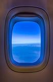 Blått ljus från himlen skiner in i flygplanfönstret Arkivbild