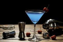 Blått martini för färgrik coctail recept med röd körsbär- och bartendertillbehör på trätabellen i svart bakgrund arkivfoto