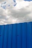 Blått metallstaket och stora vita moln Royaltyfri Fotografi