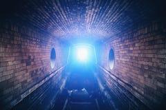 Blått mystiskt ljus på slutet av den underjordiska tunnelen för mörk tegelsten arkivbilder