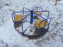 Blått- och gulingbarn som är tillkrånglade i snön, parkerar område av ‹för †staden Arkivbild