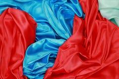 Blått och rött och ljust - grönt siden- material för textursatängsammet Royaltyfri Bild