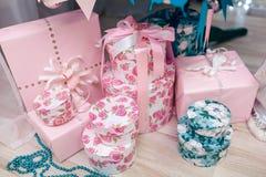 Blått och rosa färger dekorerade gåvaaskar med strumpebandsorden under den dekorerade julgranen Royaltyfri Fotografi
