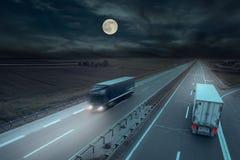 Blått och vit åker lastbil i rörelsesuddighet på midnatt Arkivfoto