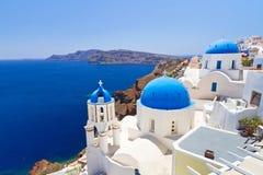 Blått- och vitkyrka av den Oia byn på Santorini Royaltyfri Bild