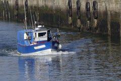 Blått och vitt kustfiskefartyg som är kommande i porten av Lorient, Frankrike med lagret i bakgrunden Royaltyfri Foto