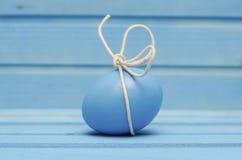 Blått påskägg med den vita pilbågen på blå träbakgrund Arkivbilder