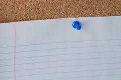 Blått papper för innehav för tummehals på Cork Board Fotografering för Bildbyråer