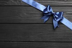 Blått pilbåge och band för gåva på en svart träbakgrund arkivbild