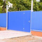 Blått port och staket arkivbilder